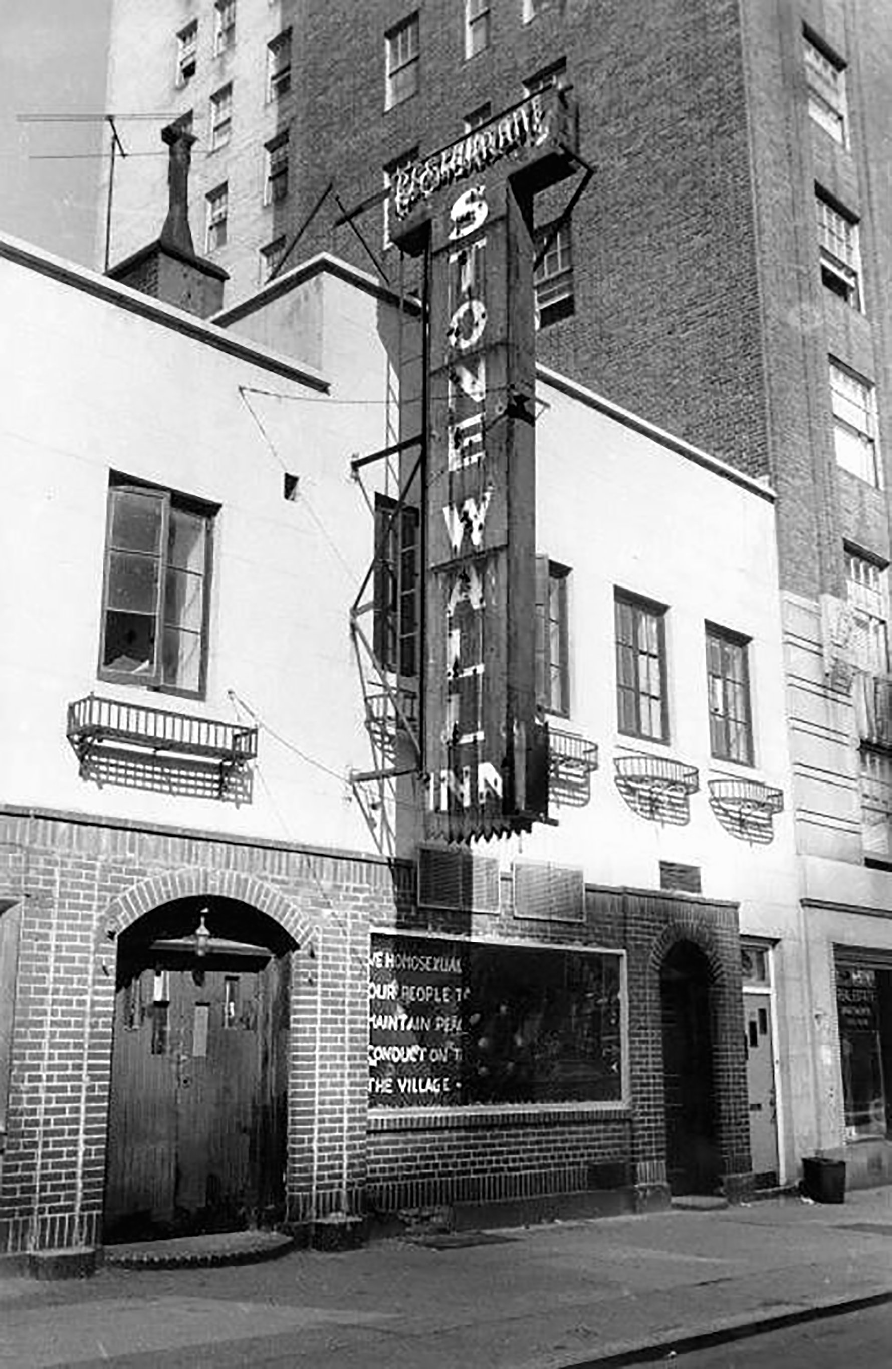 """Black and white photo of the stonewall inn, a sign reads """"STONEWALL"""""""