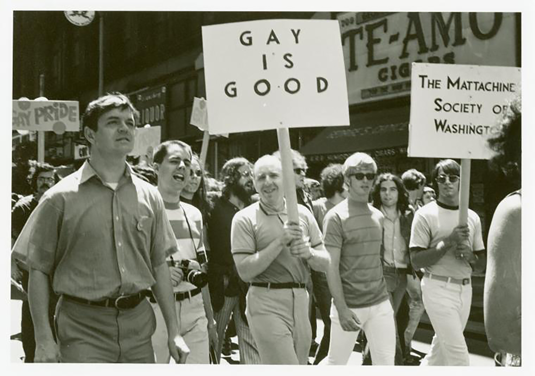 """A group of marchers, one holds a sign that reads """"GAY IS GOOD"""" another holds a sign that reads """"THE MATTACHINE SOCIETY OF WASHINGTON"""""""