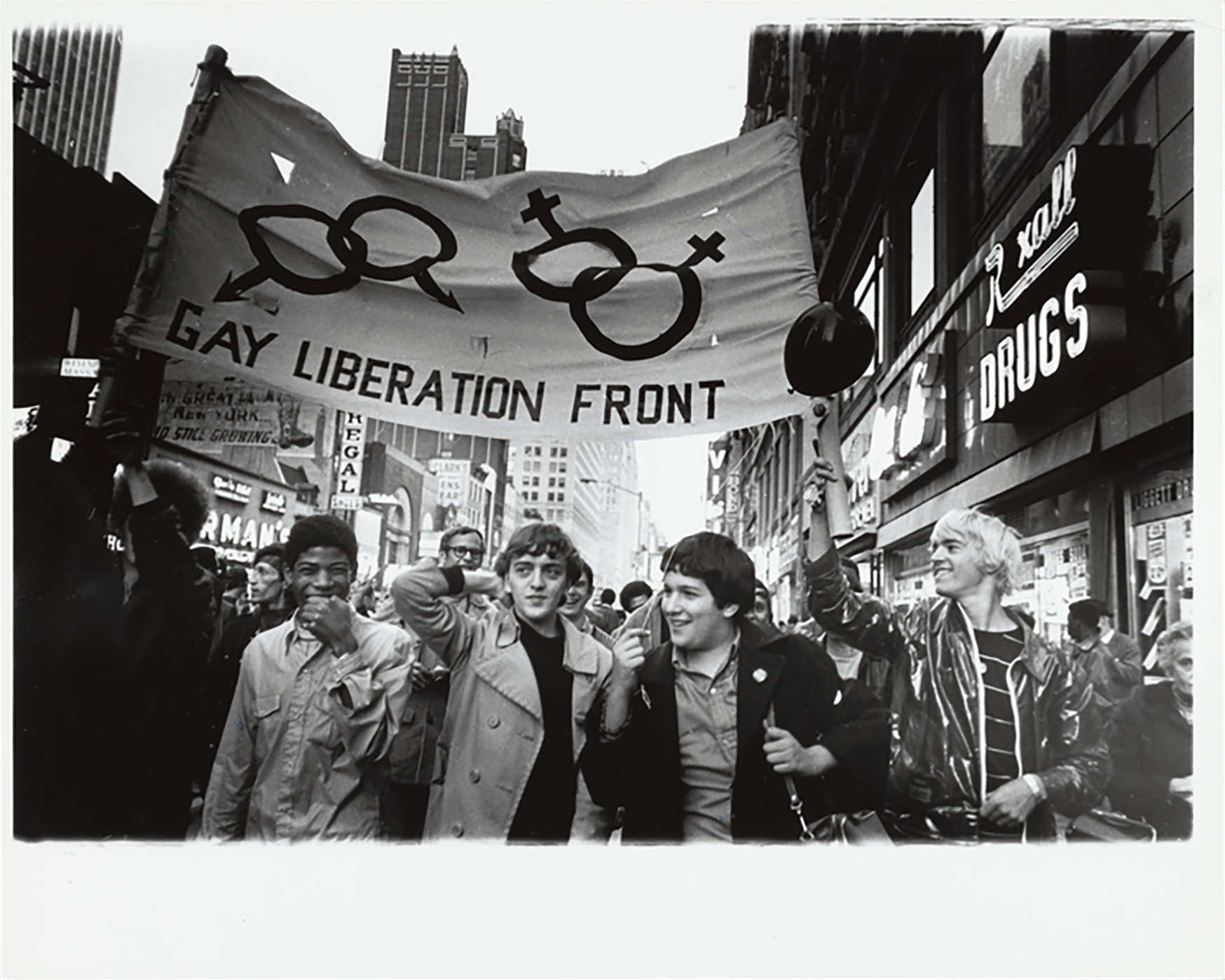 """A group of marchers holding a sign that reads """"GAY LIBERATION FRONT"""" and groups of the symbol for male and the symbol for female"""