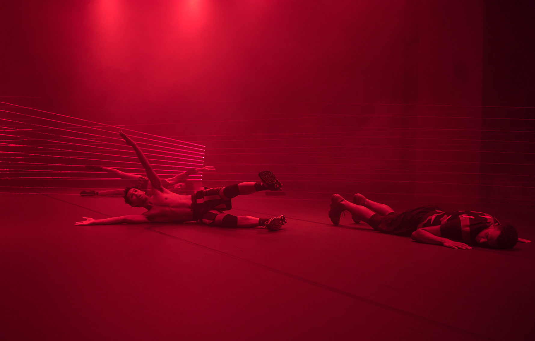 Dancers lie on the ground in a wash of red light