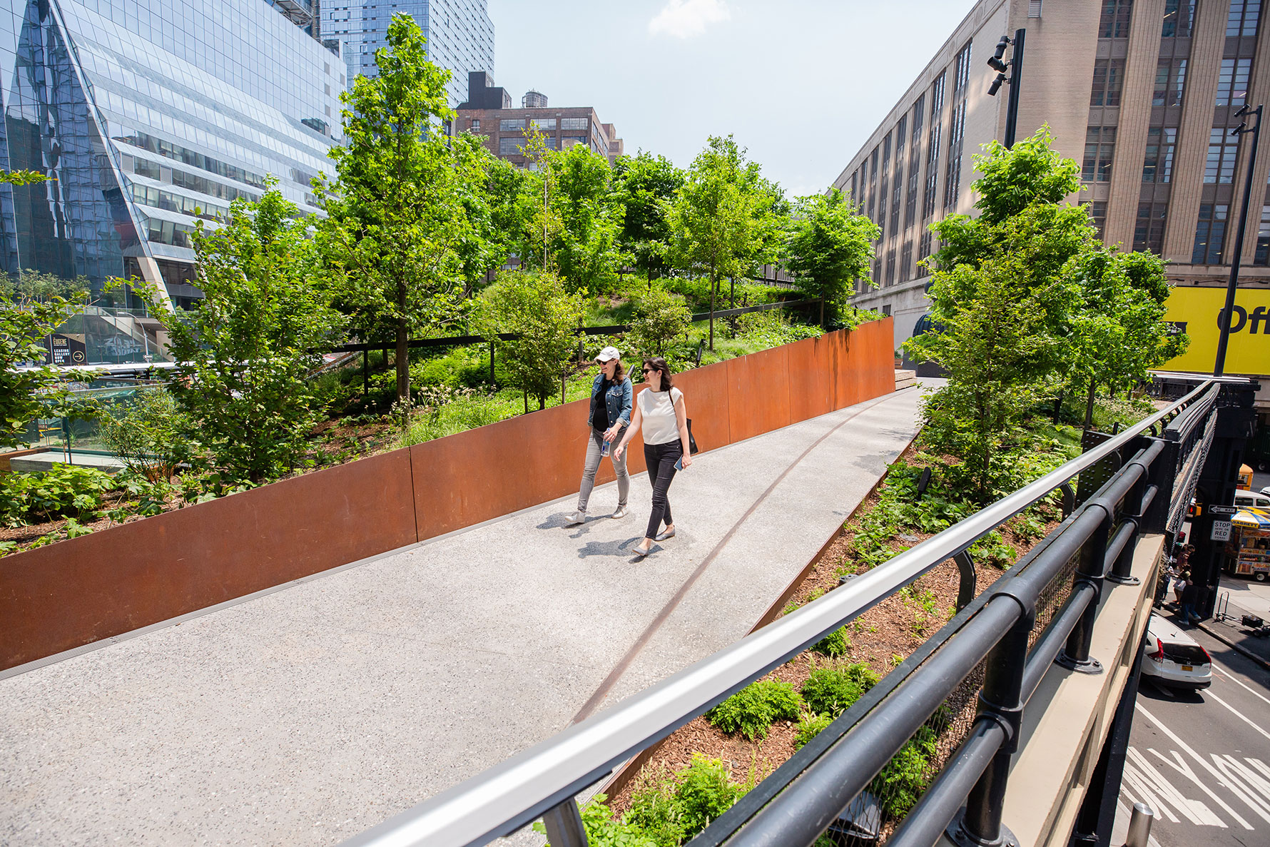 People walking on the High Line between two large planting beds