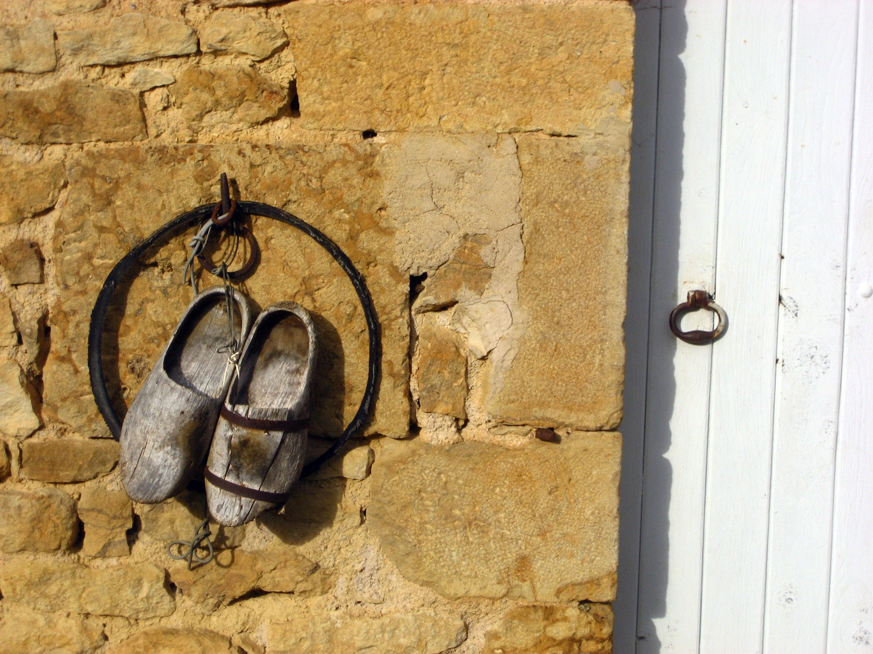 Two wooden clogs, sabots, hang from a wall