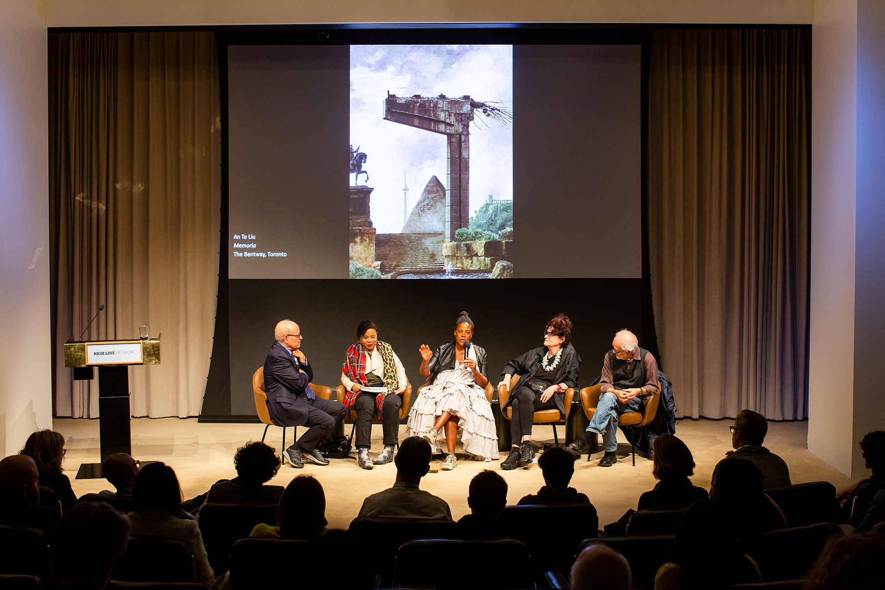 A panel discussion in front of a screen