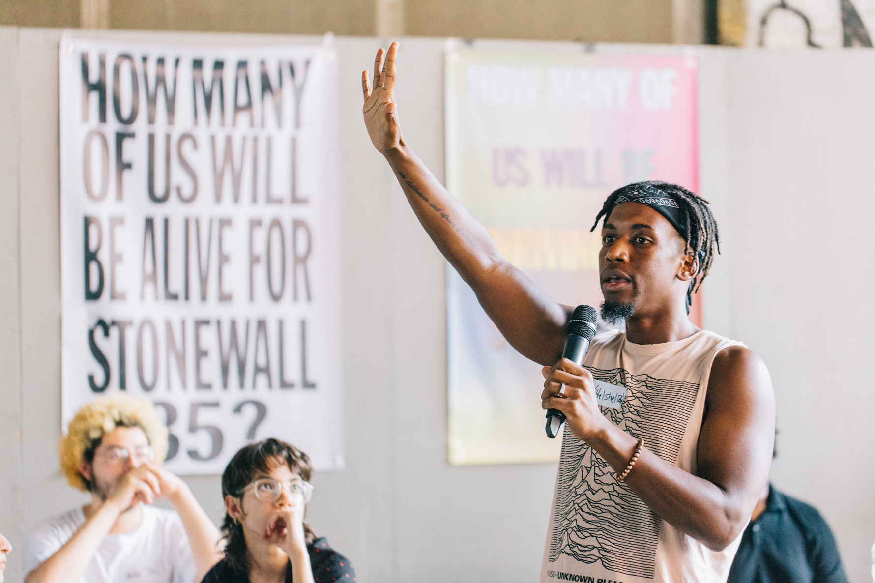 A person raising their hand in front of a poster that reads HOW MANY OF US WILL BE ALIVE FOR STONEWALL 35?