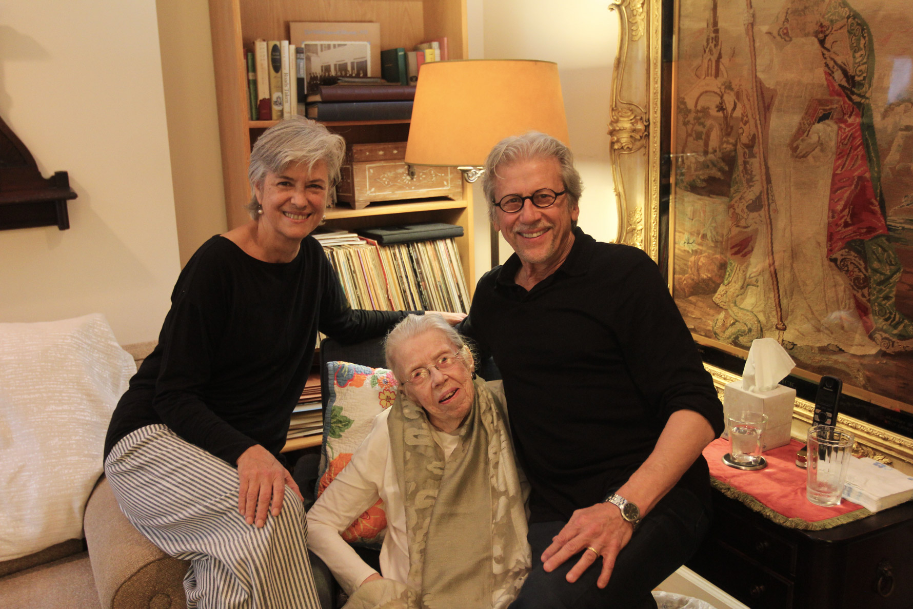 Three people posing for a camera in a living room