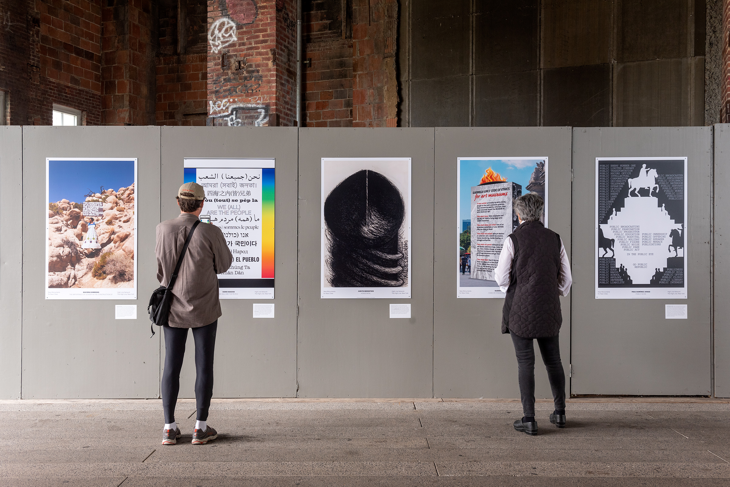People looking at posters on a wall